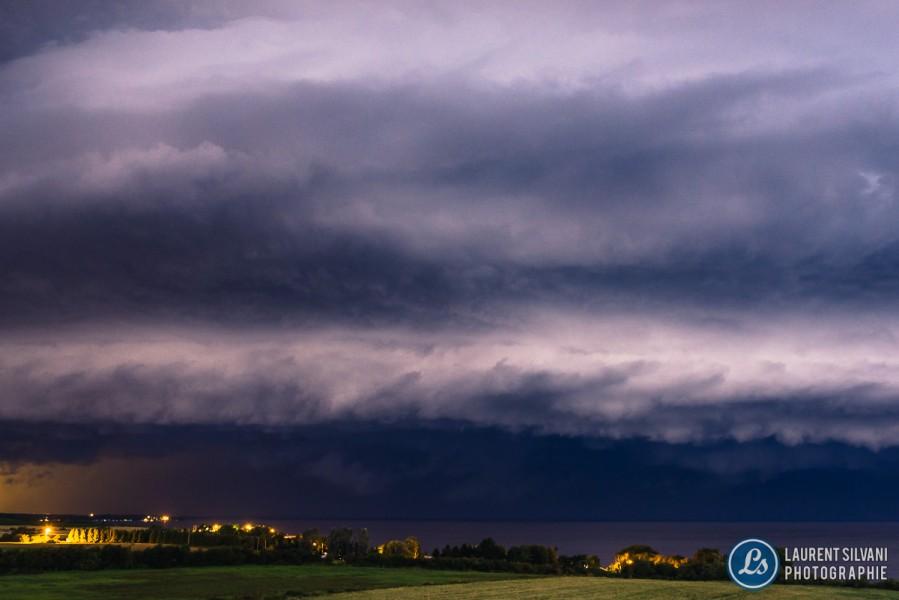 Vue surprenante d'un orage de type barrière alors qu'un éclair frappe le ciel au Lac-Saint-Jean
